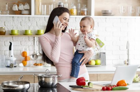 Mother talking on smartphone and holding adorable baby in kitchen at home. Work during maternity leave