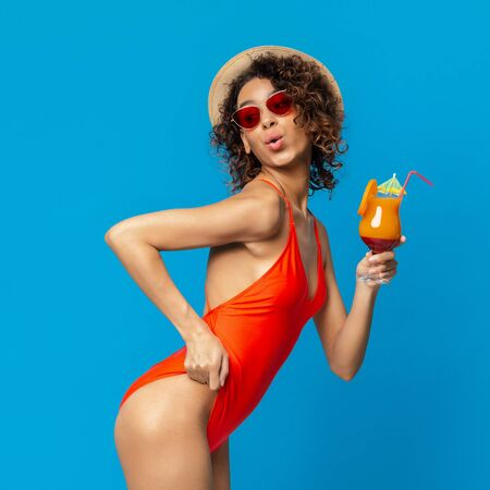 Oops. Cool african girl in swimwear holding cocktail and showing her butt, blue studio background