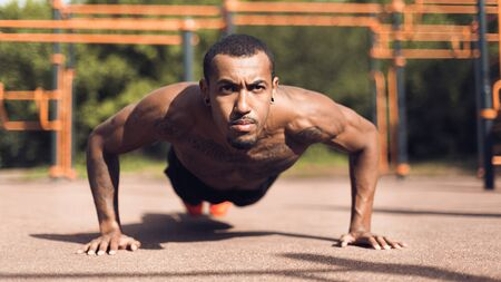 Muscular Man Doing Push Ups On Sports Ground, Working Out In Morning Stock Photo