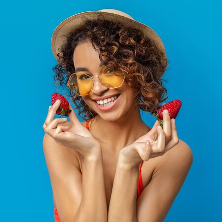 Cheerful african girl in wicker hat and sunglasses holding ripe red strawberries and smiling, blue studio background Stockfoto