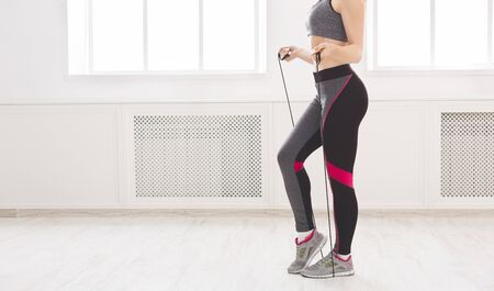 Unrecognizabke young sporty girl training with skipping rope in light studio, panorama, free space Stock Photo