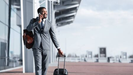 Afro Businessman Walking With Luggage And Talking On Phone, Arriving To Airport Фото со стока