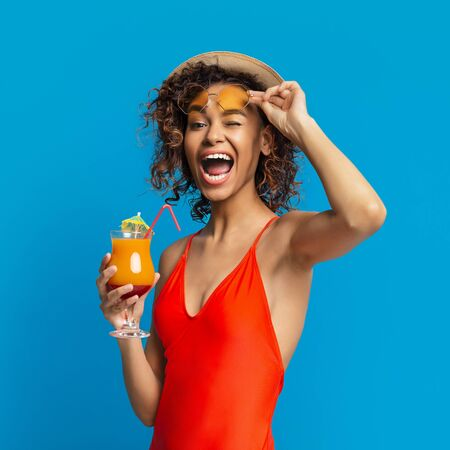 Enjoying vacation. Friendly african girl winking to camera, drinking summer cocktail, blue studio background Stockfoto