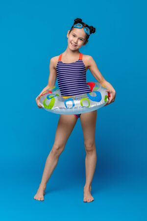 Enjoying summer vacation. Cute little girl in swimwear posing with inflatable ring and swim goggles, blue studio background