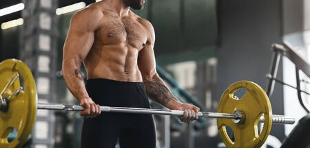Powerlifting. Muscular guy lifting heavy barbell at gym, panorama