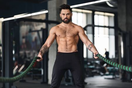 Muscular guy with naked torso exercising with battle ropes, crossfit training concept Stock Photo