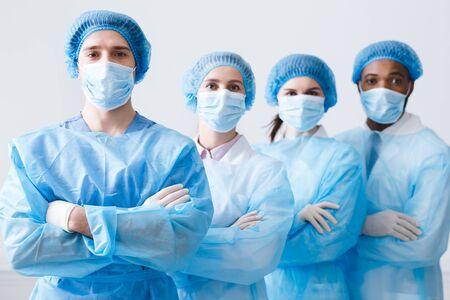 Chirurgenteam klaar voor operatie. Beoefenaars die beschermende uniformen, petten en maskers dragen Stockfoto