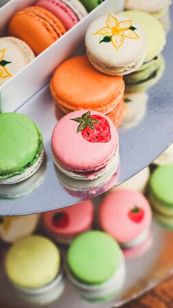 Diverse colorful macaron cookies on bar for sale, vertical panorama
