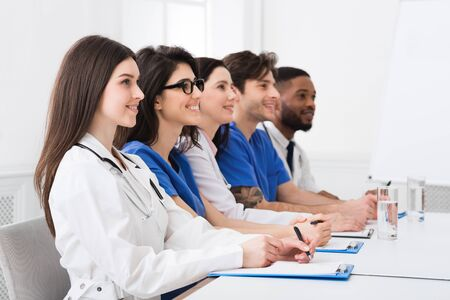 Seminarium medyczne. Lekarze i stażyści słuchają profesora w sali konferencyjnej Zdjęcie Seryjne