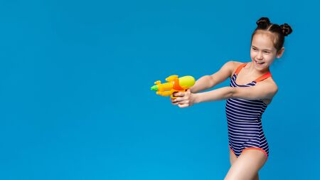 Cheerful girl in swimwear shooting aside with water gun, blue panorama background with empty space Foto de archivo