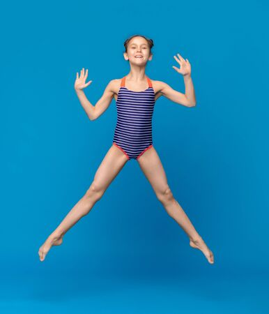 Emotional little girl in swimsuit jumping in air on blue studio background