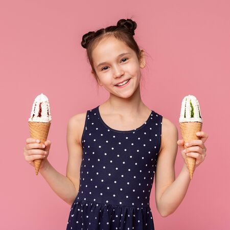 Enjoy it. Cheerful girl offering two ice cream cones, smiling on camera, pink studio background