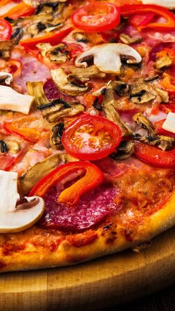 Delicious pizza with mushrooms and pepperoni on wooden platter, vertical panorama Stock Photo
