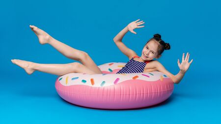 Summer relax. Happy little girl swimming on donut shaped pink inflatable ring, blue panorama background