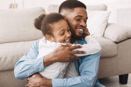Ik hou van je papa! Schattige dochter knuffelt vader met liefde en tederheid thuis