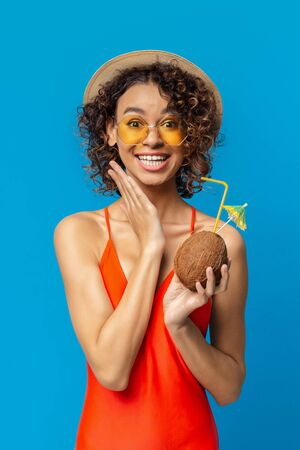 Omg. Excited black girl in swimwear holding tropical cocktail in coconut shell, blue studio background Stockfoto