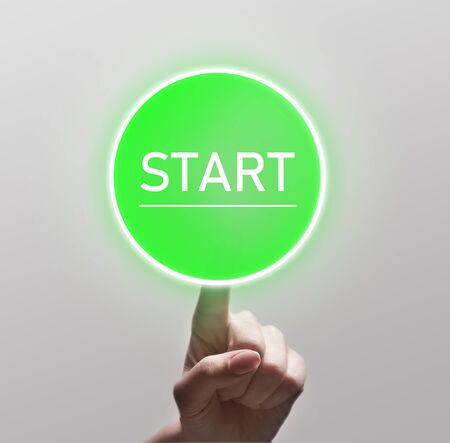 Finger touching green start button on light background, copy space