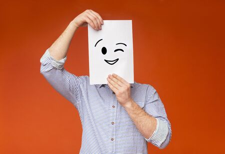Young guy hiding his face under painted winking smile on white paper, orange background, panorama
