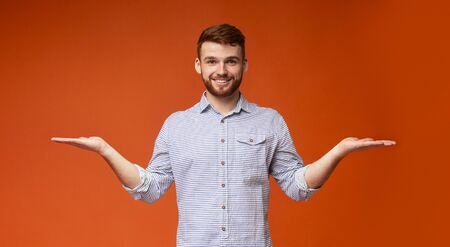 Young millennial guy propose to choose the best variant from his palms with free space on orange background, panorama