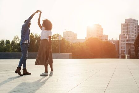 Romantic couple dancing at sunset and having fun, walking in the city, copy space Stock Photo