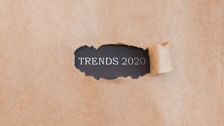 Trends 2020. Modern gold text on black opening under torned brown paper, panorama, free space