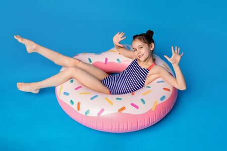 Sea relax. Happy little girl lying on donut shaped pink inflatable ring, blue panorama background