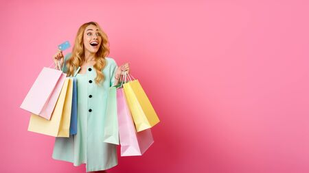 Consumerism Concept. Girl Holding Credit Card And Shopping Bags, Pink Background