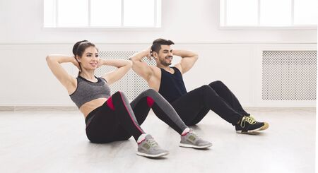 Young active couple doing sport exercises on the floor in white studio, panorama, copy space