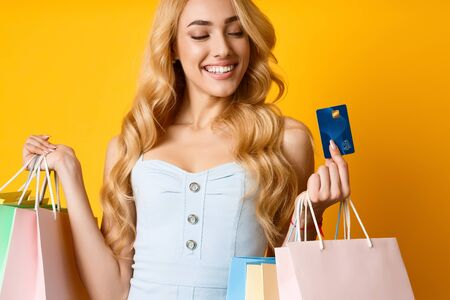 Shopping Concept. Young Shopaholic Showing Debit Card On Yellow Studio Background