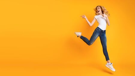 Joyful Woman Jumping And Pointing At Copy Space On Yellow Background