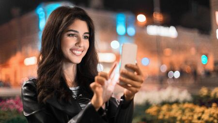 Happy woman sending message on phone, walking at night in the city Stock Photo