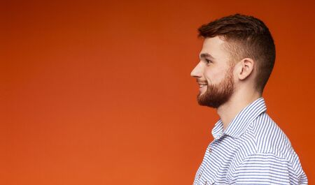 Side view portrait of smiling millennial man looking away at copy space on orange background, panorama
