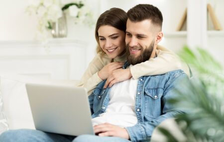 Loving Couple Having Video-Call On Laptop, Woman Hugging Husband, Relaxing At Home Stock Photo