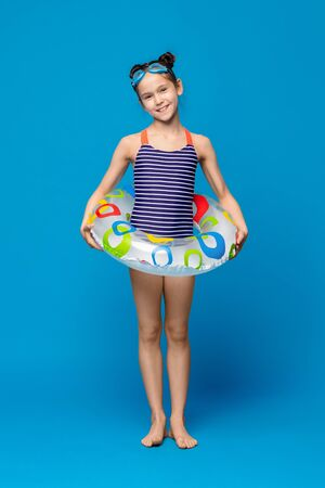 Little mermaid. Cute girl in swimwear smiling with inflatable ring and swim goggles, blue studio background