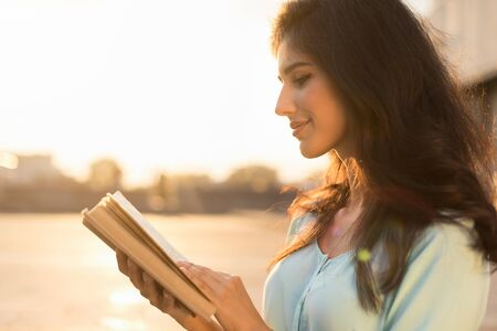 Girl reading book outdoors, walking on city street at sunset, enjoying calm evening Stock Photo