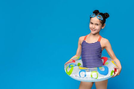 Little girl wearing inflatable ring and swim goggles, blue panorama background with empty space