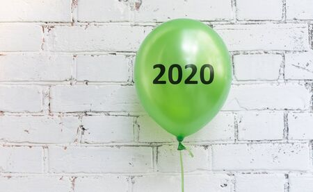 Eco concept. Close up of green balloon with 2020 text on white wall background, panorama, copy space