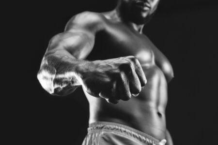 Muscular african bodybuilder demonstrating his fist and vein, black and white studio photo