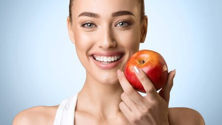 Stomatology Concept. Woman With Perfect Smile Holding Red Apple, Blue Background