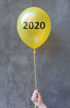 Celebrating 2020. Yellow balloon in woman hand on concrete background, vertical panorama, copy space