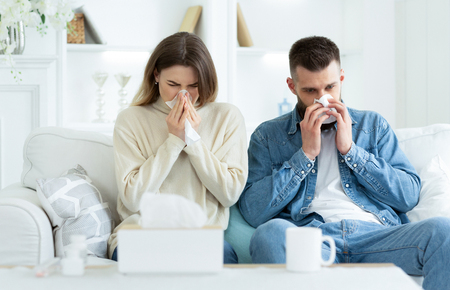 Couple Suffering From Cold, Blowing Noses And Sneezing, Sitting On Sofa At Home Stok Fotoğraf