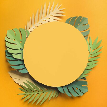 Summer background with yellow round blank place surrounded by Exotic leaves, paper photo