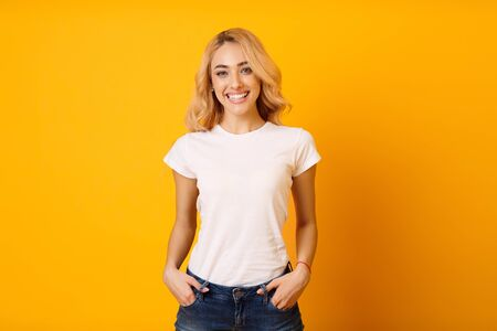 Mockup. Millennial Woman In White T-Shirt On Yellow Background, Posing To Camera Stok Fotoğraf
