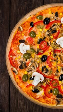 Italian pizza with ham, tomatoes and black olives on wood, top view, vertical panorama