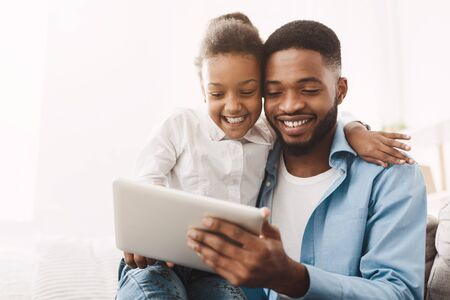 Watch Cartoon On Tablet. Father And Daughter Using Digital Device At Home Banque d'images - 125080116
