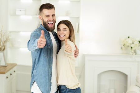 Young Couple Showing Thumbs Up In New House, Moving Concept, Copy Space