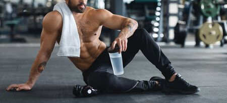 Little break. Naked man holding water bottle, sitting on floor at gym, panorama Stock Photo