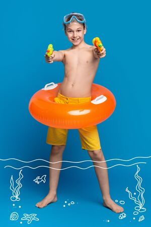 Rest at seaside. Cheerful teenage boy resting in water, shooting with water guns at camera, blue studio background