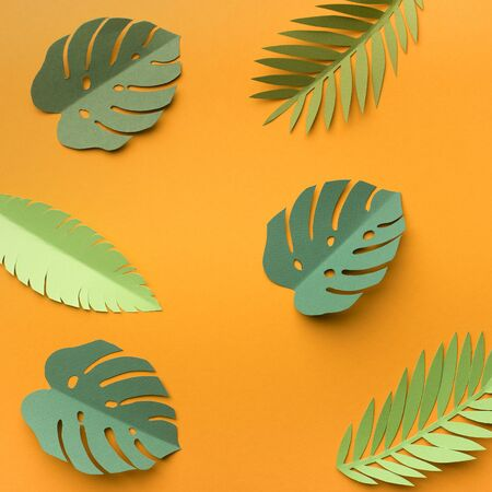 Summer background with tropical green leaves on yellow, paper photo Stok Fotoğraf