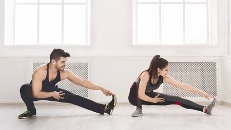 Sporty couple stretching legs before training in studio, panorama, copy space
